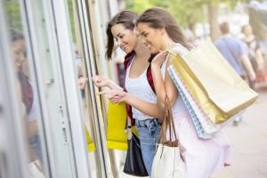 doua femei merg bucuroase la mall pentru a cumpara rochii